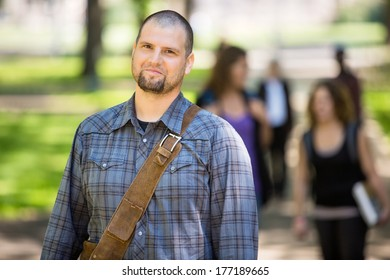 Portrait of confident male student at campus with friends in background