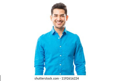 Portrait of confident male wearing blue shirt while standing on plain background