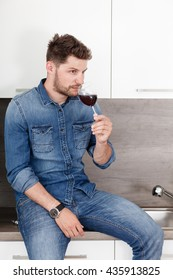 Portrait of a confident man in a denim shirt. A man with a glass of red wine in modern kitchen.