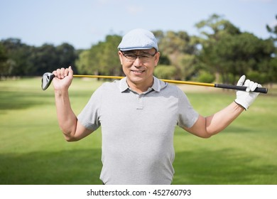 Portrait of confident man holding golf club while standing on field