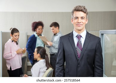 Portrait of confident manager with employees discussing in background at call center