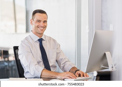 Portrait of confident manager sitting at desk and looking at camera. Portrait of smiling business man working at computer. Successful formal man in his new modern office.