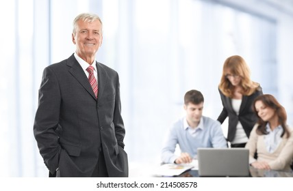 Portrait of confident manager standing at office with colleagues at background.