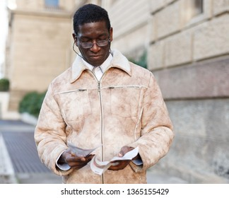 Portrait of confident mature African man in overcoat reading guidebook near Museum