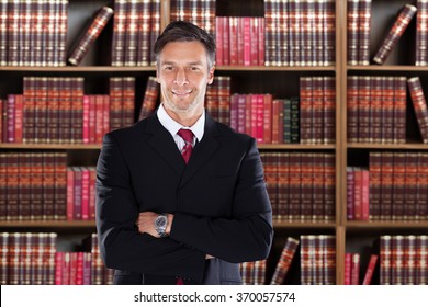Portrait of confident mature attorney standing arms crossed against bookshelf in office