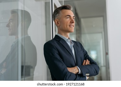 Portrait of confident mature businessman with arms crossed planning start up standing in office. Successful business