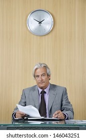 Portrait of a confident mature businessman with documents at desk in office