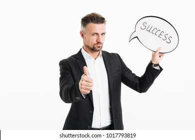 Portrait of a confident mature businessman dressed in suit holding speech bubble with word success and showing thumbs up gesture isolated over white background