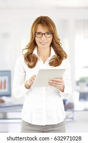 Portrait of a confident mature businesswoman using her digital tablet while working in the office.