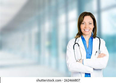 Portrait confident mature female doctor medical professional standing isolated on hospital clinic hallway windows background. Positive face expression