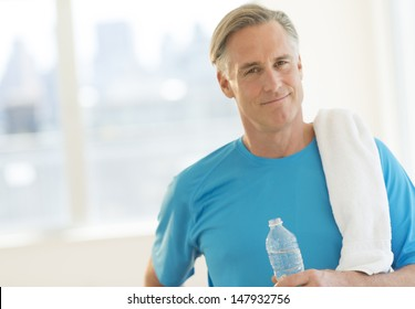 Portrait of confident mature man with towel and water bottle at health club