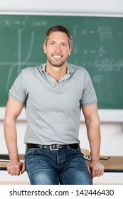 Portrait of confident mature teacher leaning on bench in classroom