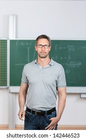 Portrait of confident mature teacher standing in classroom