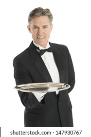 Portrait of confident mature waiter in tuxedo carrying serving tray against white background