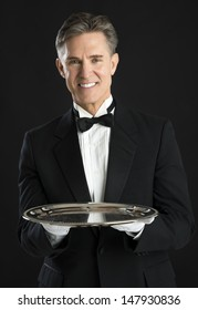 Portrait of confident mature waiter in tuxedo with serving tray standing against black background