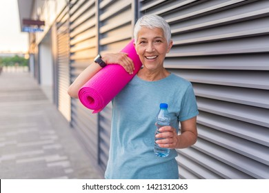 Portrait of confident mature woman with exercise mat smiling. Woman holding rolled up exercise mat. Happy mature woman with a yoga mat. Fit Senior Woman With Exercise Mat