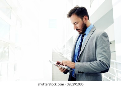 Portrait of a confident men entrepreneur dressed in expensive suit working on digital tablet while standing in modern office interior, intelligent male lawyer working on touch pad during work break