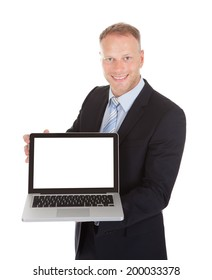 Portrait of confident mid adult businessman displaying laptop over white background