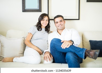 Portrait of confident mid adult man sitting by pregnant wife on sofa