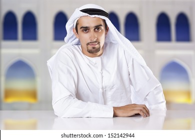 Portrait of a confident Middle Eastern businessman sitting and looking at the camera.