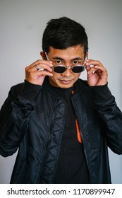 A portrait of a confident, middle-aged and handsome Malay Muslim Singaporean Asian man. He is wearing a casual black jacket and sunglasses for his portrait head shot and is smiling softly.