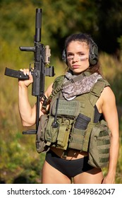 portrait of confident military woman with a gun in forest, hunter female in camouflage suit with a gun stand in nature alone