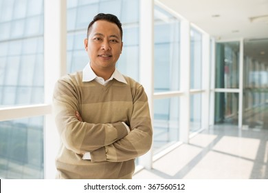 Portrait of confident mixed-race businessman standing with his arms crossed