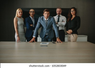 Portrait of confident multi ethnic group of businesspeople looking at camera while standing together at conference table. Corporate professionals in office meeting room.