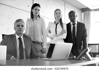Portrait of confident multi-ethnic business people at desk in office