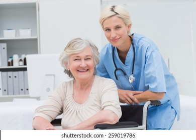 Portrait of confident nurse leaning on senior patients wheelchair at clinic