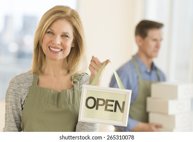 Portrait of confident owner wearing apron while holding open sign in coffeeshop