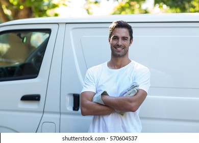 Portrait of confident painter with arms crossed standing against van