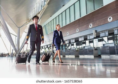 Portrait of confident pilot with stewardess walking in airport