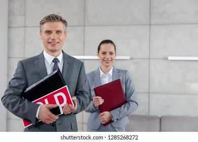 Portrait of confident realtors holding documents against wall in apartment