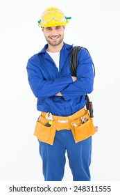 Portrait of confident repairman standing arms crossed against white background