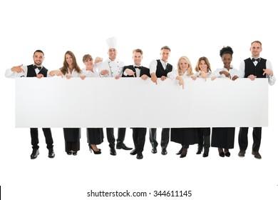 Portrait of confident restaurant staff holding blank billboard against white background