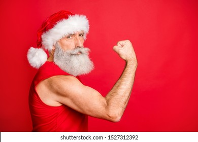 Portrait of confident santa claus show his trainign his triceps wearing trendy sportswear hat cap isolated over red background