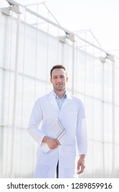 Portrait of confident scientist with clipboard outside greenhouse