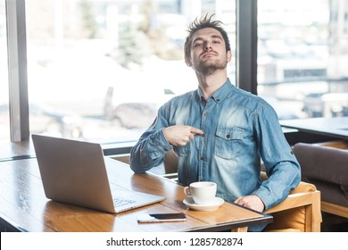 Portrait of confident selfish satisfied egoistic bearded young freelancer in blue jeans shirt are sitting in cafe, working on laptop and pointing finger at himself with pride. indoor, inside