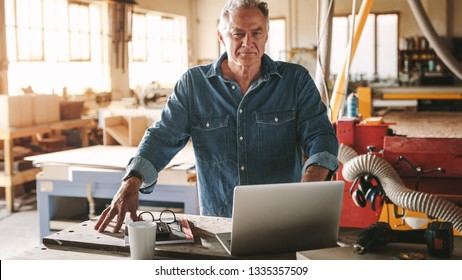 Portrait of confident senior male carpenter standing by his workbench looking at camera. Mature male carpenter in his workshop with laptop on table.