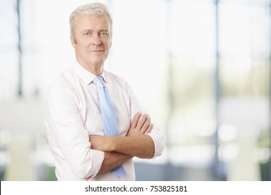 Portrait of a confident senior man standing with arms crossed indoor.