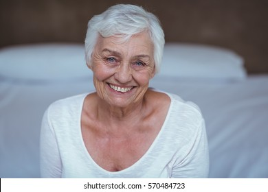 Portrait of confident senior woman on bed in room