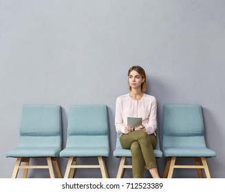 Portrait of confident serious young European female sitting on chair in waiting room with electronic tablet, setting her mind up before job interview or meeting with potential business partners