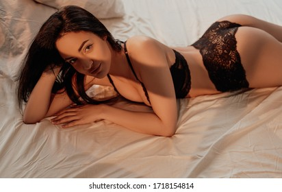 Portrait of a confident and sexy female model with brown hair wearing black lingerie while laying on bed among sheets and pillows, smiling and showing her buttocks