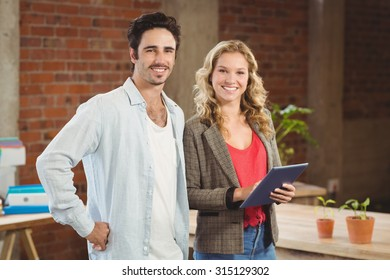 Portrait of confident smiling business people standing in creative office