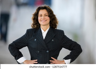 Portrait of a confident smiling business woman with her hands on hips on a street in the city.
