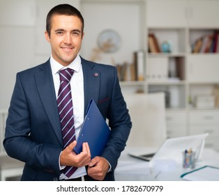 Portrait of confident smiling businessman standing in office, holding folder with documents