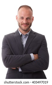 Portrait of confident smiling businessman standing arms crossed, looking at camera.