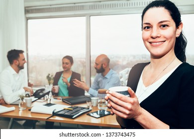 portrait of a confident smiling businesswoman in office with working colleagues on background