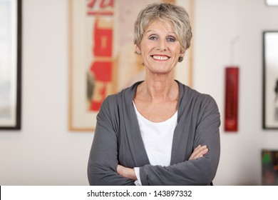 Portrait of a confident smiling senior woman standing with arms crossed at home